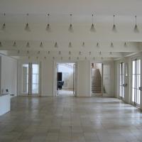 Türe: Das Foyer mit den Leuchten im Raster und den zweiflügligen Eingangstüren (aus Kunststein)