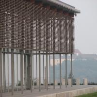 Fassade: Fassade aus Holzlamellen im Hintergrund die Burg (aus Glas)