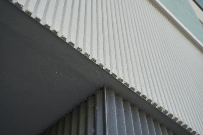 Detail nach Titel: Übergang Putzband mit RIllen zu Metallverkleidung im Erdgeschoss (aus Putz und Metall)