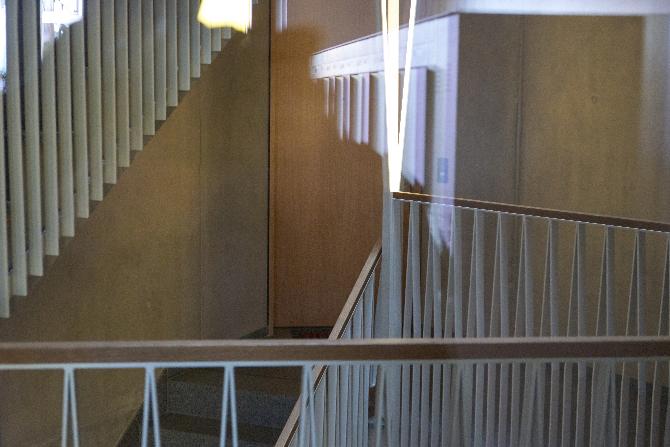 Erschliessung: Treppenhaus mit schiefen Stahlstaketen und schrägen trapezförmigen Leuchten (aus Metall)