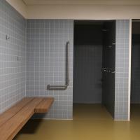 Sanitär: Behindertengerechte Duschen Turnhalle mit farbigen hellblauen Plättli (aus Keramik)
