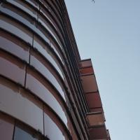Fassade: Die farbigen Glaslamellen mit den Klappen für den Sonnenschutz (aus Glas)