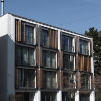 Fassade: Fassade mit Holzschiebefaltläden und klar gegliederter Fassade