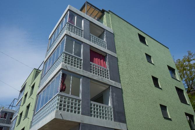 Aussenraum: Die Loggien mit den roten Vorhängen von Aussen (aus Beton und Glas)
