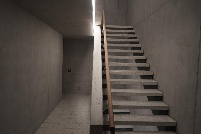 Erschliessung: Treppenhaus in Sichtbeton mit Kunststeinplatten und Beleuchtung in Spalt integriert (aus Beton und Kunststein)