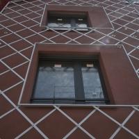 Garage: Rote Fassade mit Rankgitter aus Aluminium (?) giebelseitig (aus Putz und Metall)