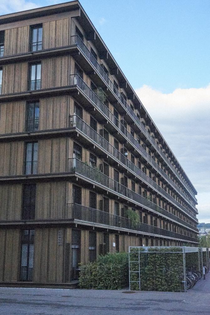 Blick entlang der Fassade aus Holz mit den regelmässigen Fenstern