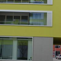 Fassade: Liegende Fensterbänder und abgesetztes Sockelgeschoss (aus Putz)
