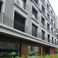 Fassade: Sicht entlang der Fassade mit abgesetzem Erdgeschoss (aus Metall und Keramik)