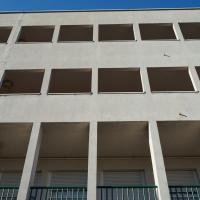 Fassade: Die recht schmucklose Fassade von Aussen mit den Laubengängen