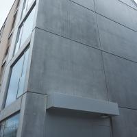 Türe: Ansicht von der Seite mit Eingangstür und Vordach (aus Beton und Metall)