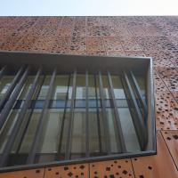 Geländer: Gelochte Cortenfassade mit Ausschnitt für Fenster (aus Metall)