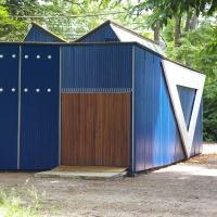 Fassade: Blau-weisse Holzschalung mit dunkelbrauner Tür (aus Holz)
