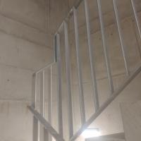 Erschliessung: Treppenhaus mit weisser Holzdecke und Metallgeländer