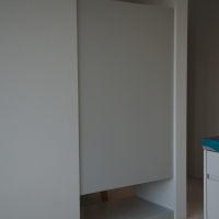 Einbauten: Rückseite der Garderobe mit Revisionsdeckel darunter