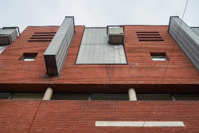 Fassade: Faasade mit spielerischen Vor- und Rücksprüngen (aus Mauerwerk und Metall)