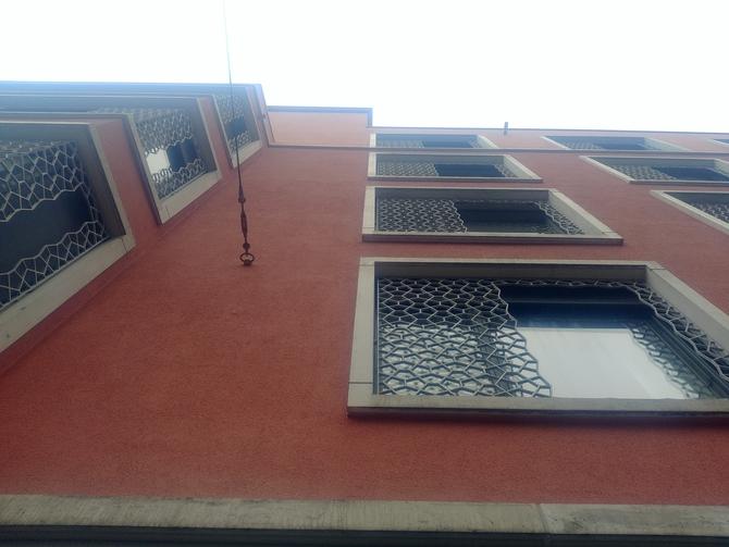Geländer: Rote Putzfassade mit Metallgitter als Verzierung (aus Metall)